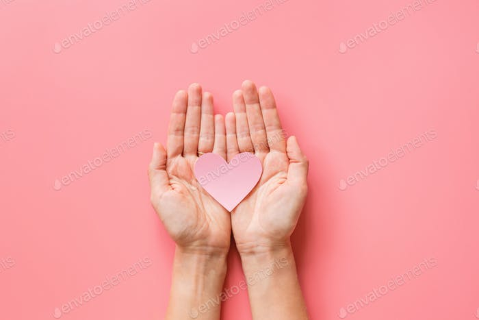 Hands holding heart on pink background. Happy Valentine's Day, health care, insurance and kindness