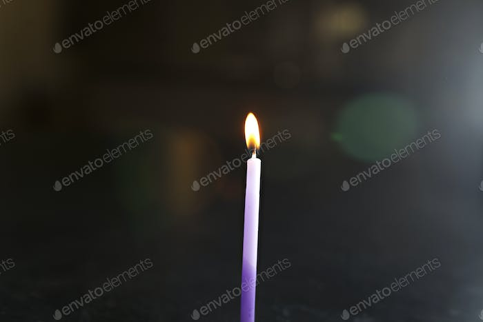 purple lit candle in the dark