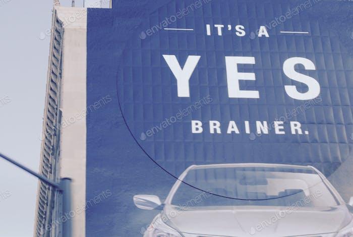 A car ad on the side of a building says It's A YES Brainer.