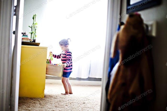 Girl looking in yellow dresser