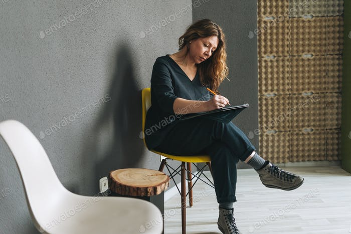 Woman on yellow chair in office
