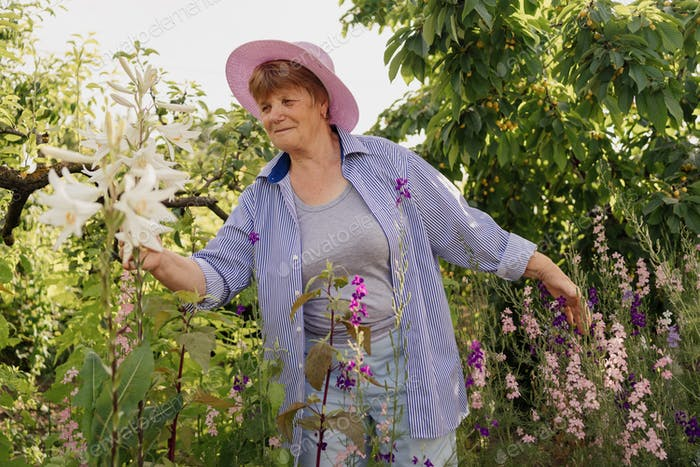 Lovely smiling senior woman enjoys flowers and trees in the garden