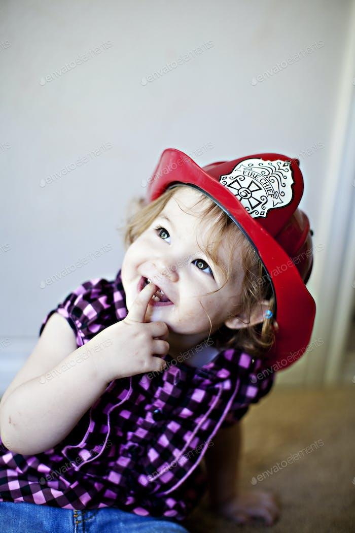 Toddler girl wearing a fireman hat