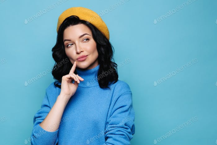 Serious brunette woman in yellow beret thinking, having tricky plan in mind, looking away. Studio.