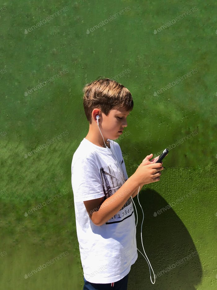 Young boy listening music against green wall  Nominated!