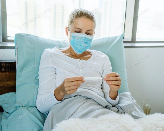 Frau überprüft ihre Temperatur