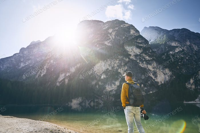Young photographer holding camera against Lake Braies and mountains during sunrise. Dolomites, Italy