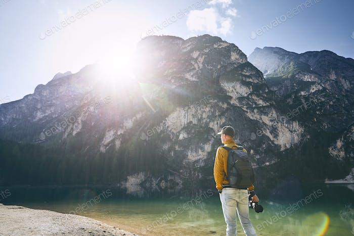 Junge Fotograf hält Kamera gegen Pragser See und Berge bei Sonnenaufgang. Dolomiten, Italien