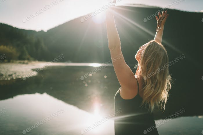 A young woman opening her arms towards the sun.
