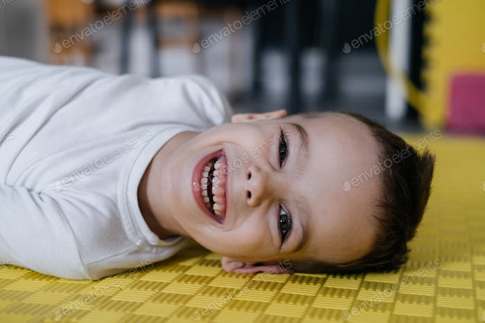 Cute little child disabled boy on mat. Child cerebral palsy