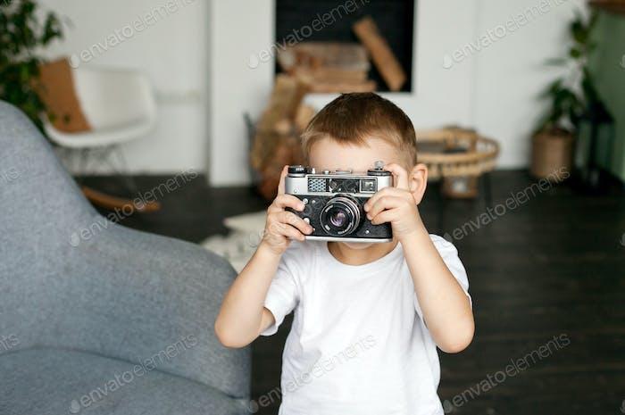 A kid taking a photo with retro camera, plain white t shirts, kids using technology, taking photos