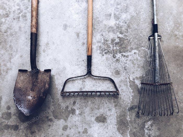 A set of three garden tools on a gray cement surface. Rakes, shovel, spade