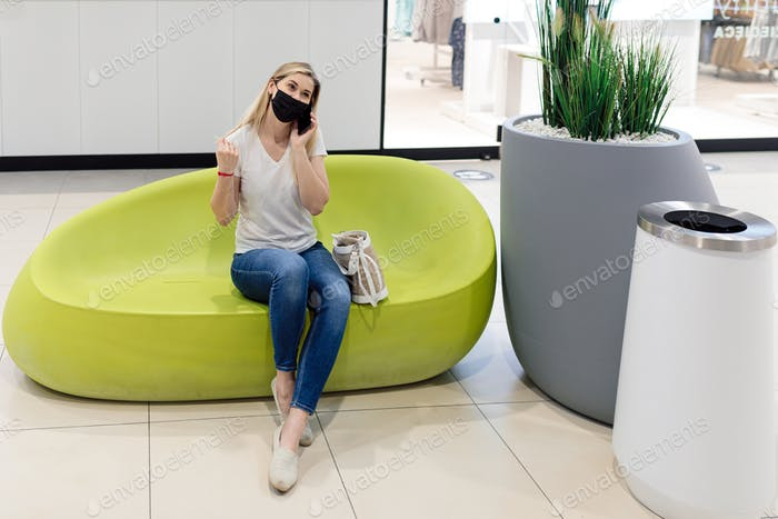 Charming young woman in personal protective mask in shopping center using mobile phone