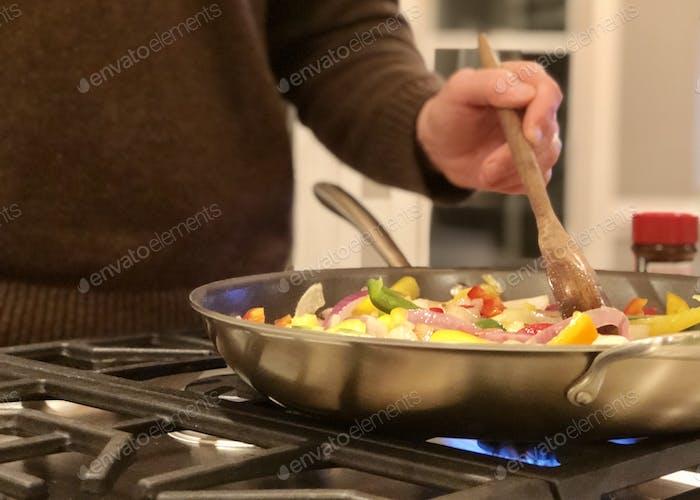 Man sautéing vegetables