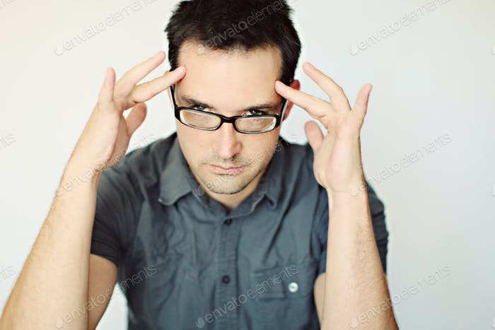 Mind control. Guy with fingers in his temples pretending to read your mind.