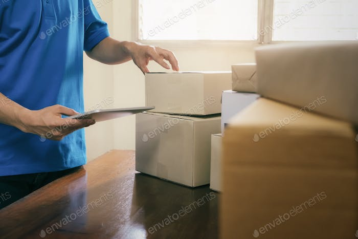 deliveryman working checking order to confirm before sending customer in post office