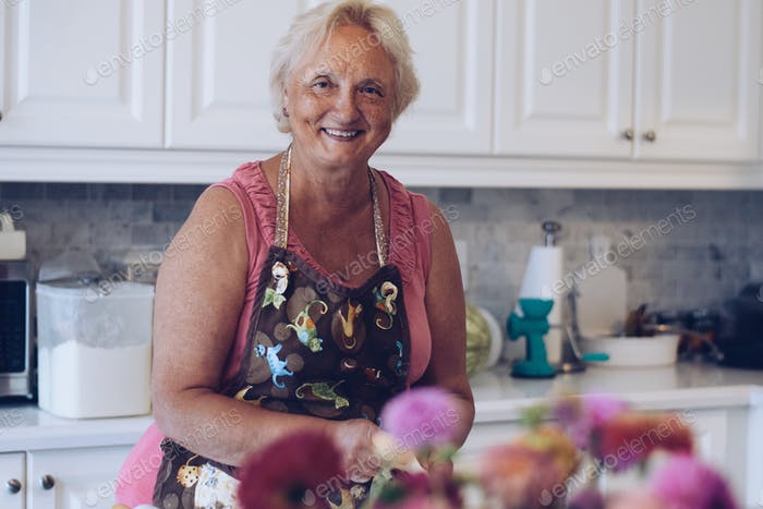 A candid portrait of a woman smiling while baking in a bright modern kitchen, Seniors lifestyle