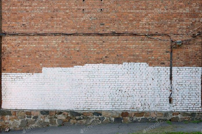 Pared residencial con parches de pintura blanca que cubren el vandalismo de graffiti en el exterior