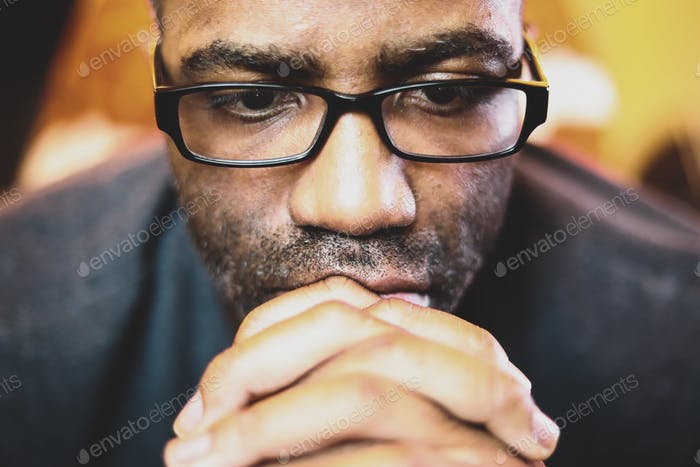 Man with glasses deep in thought with hands folded