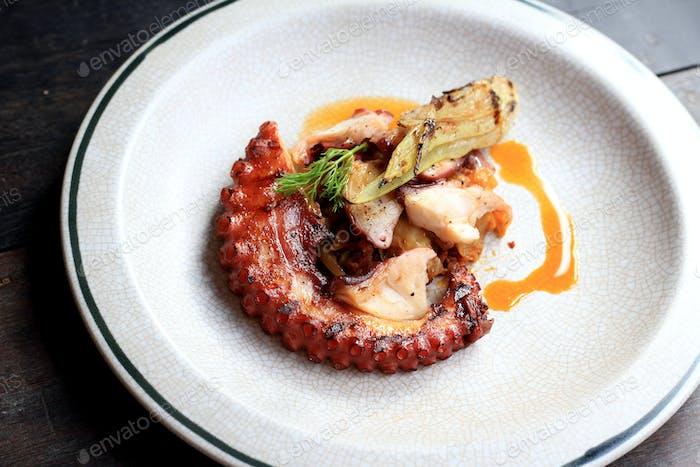 Gegrillte Oktopus-Tentakel mit Zitronen- und Petersilienblättern auf Gericht.