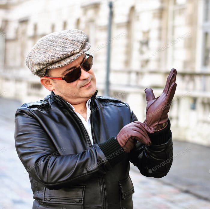 Man wearing hat, leather jacket and gloves