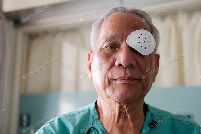 patient covering eye with protective shield & medical plaster after eyes cataract surgery in