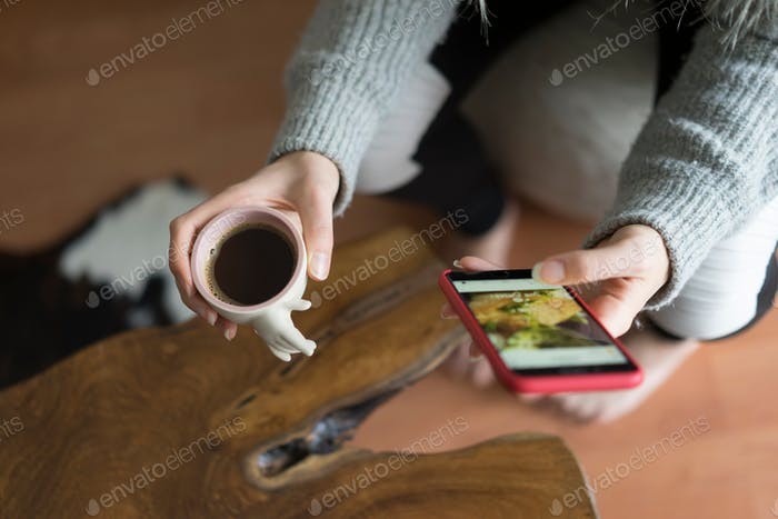 Person using mobile phone while enjoying morning coffee