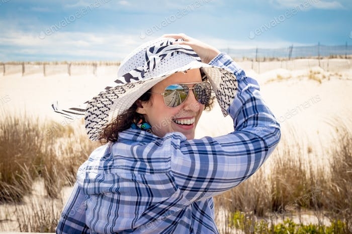 Woman at the beach holding a hat