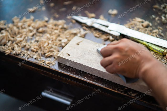 sanding wooden plank with chisel, wood dust everywhere