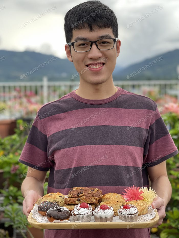 Portrait of an Asian youth holding a tray of food