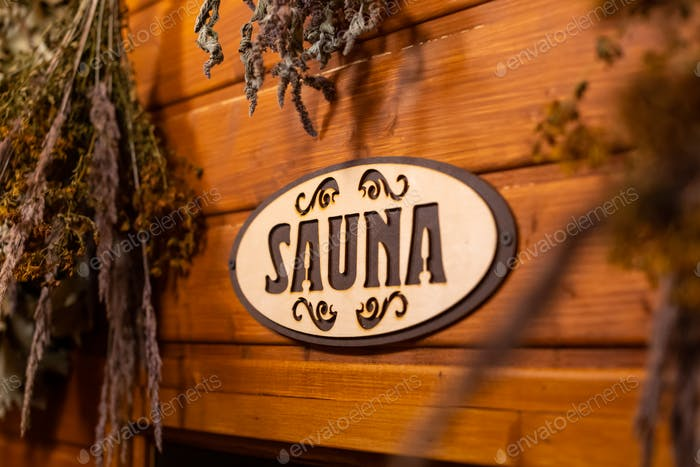 Dried herbs on wooden background with inscription sauna
