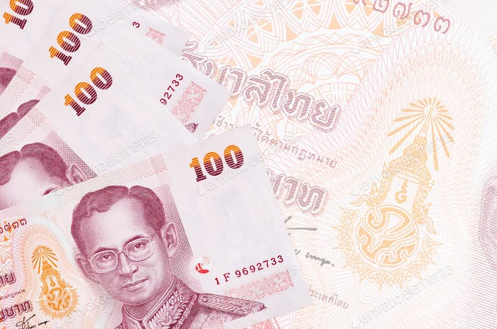 100 Thai Baht bills lies in stack on background of big semi-transparent banknote. Abstract business