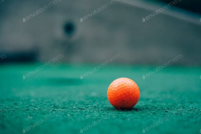 An orange golf ball on green turf.
