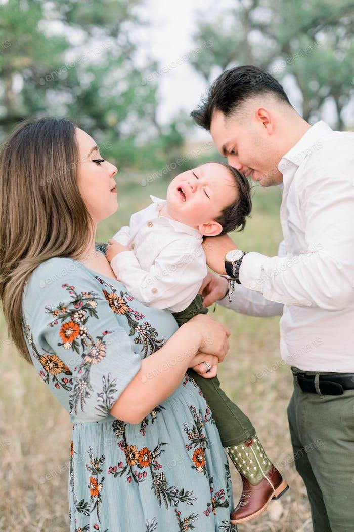 Familia de tres personas tratando de tomar retratos y el niño está teniendo una rabieta