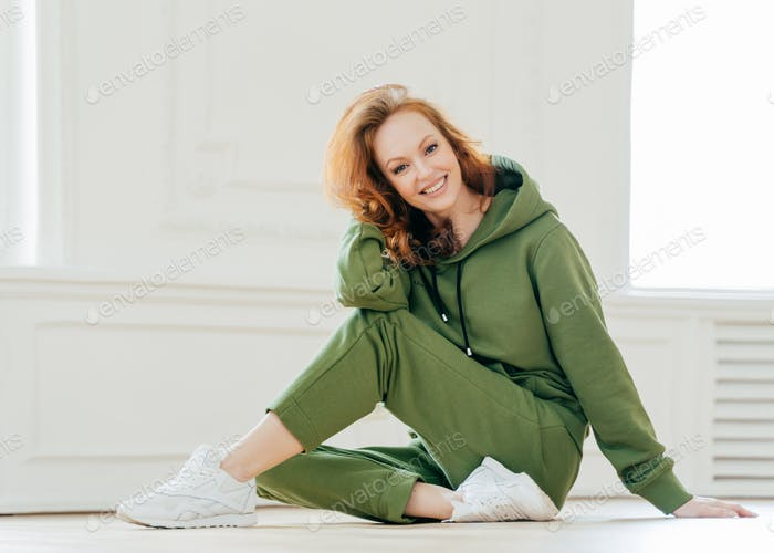 Delighted happy foxy woman busy with stretching pilate exercises in fitness studio