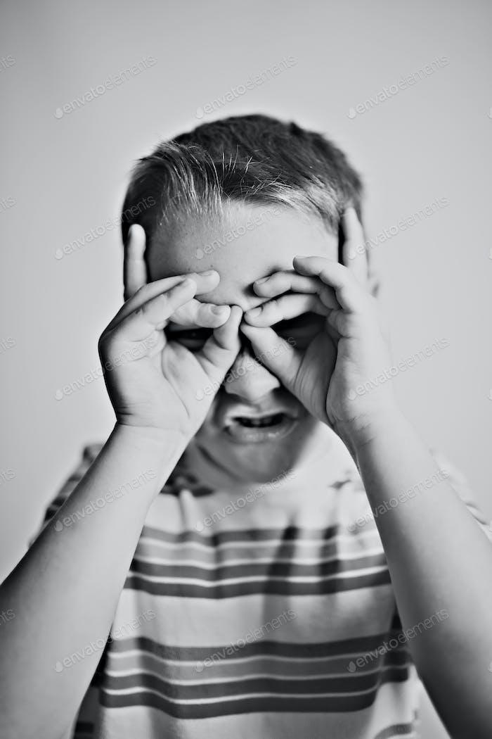 Junge macht Schutzbrillen um seine Augen mit seinen Händen während eines Porträts