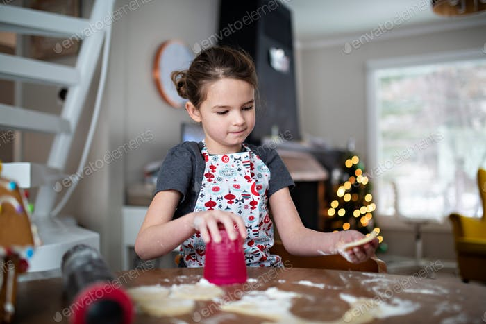young girl cutting out Christmas cookies