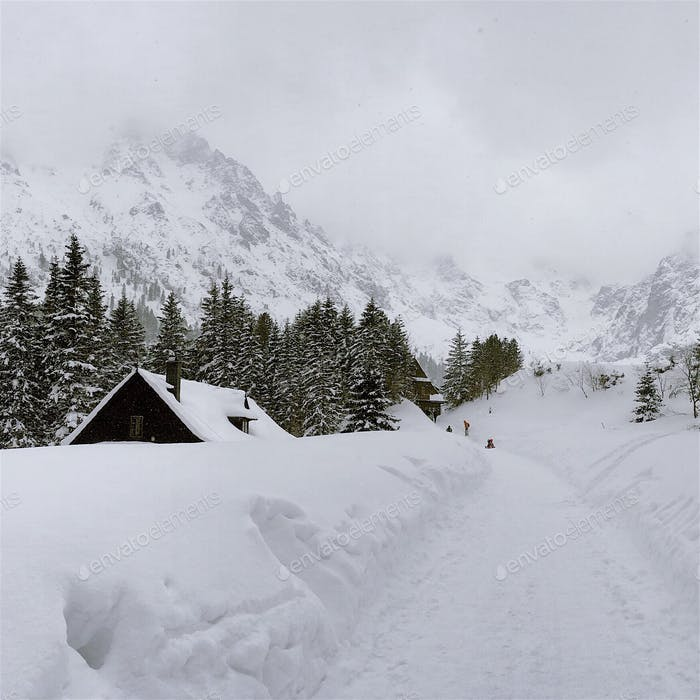 Winter landscape. Wooden chalet in the snow surrounded by mountains
