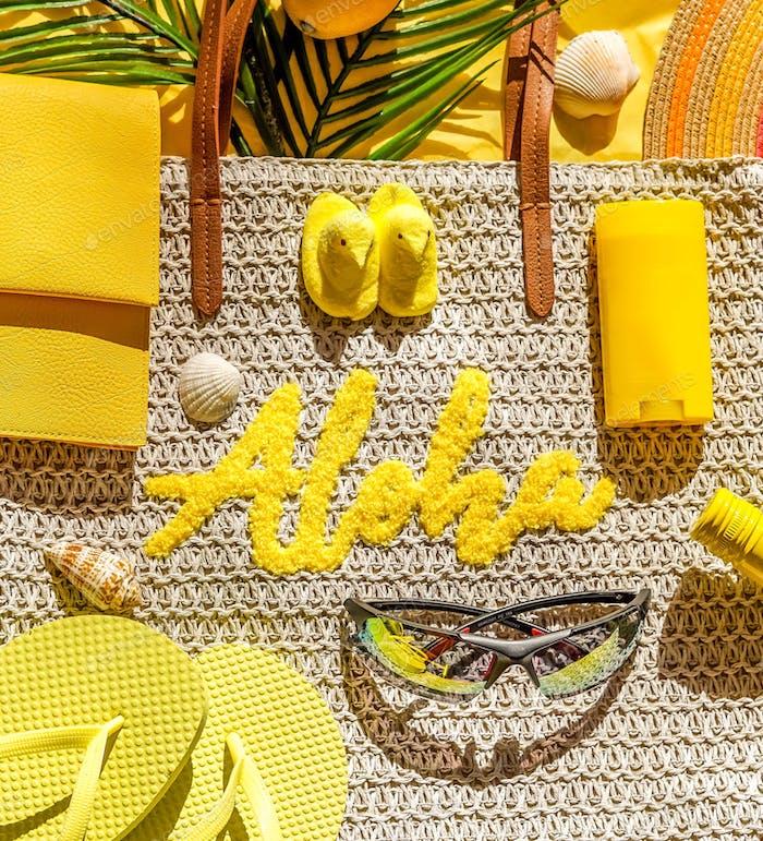 Yellow flatlay of beach items like Aloha tote, sunscreen, flip flops, sunglasses