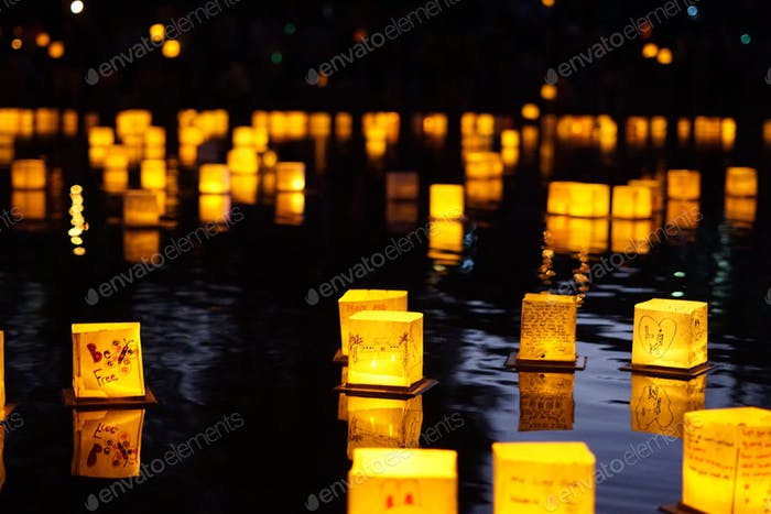 Illuminated paper lanterns floating on water