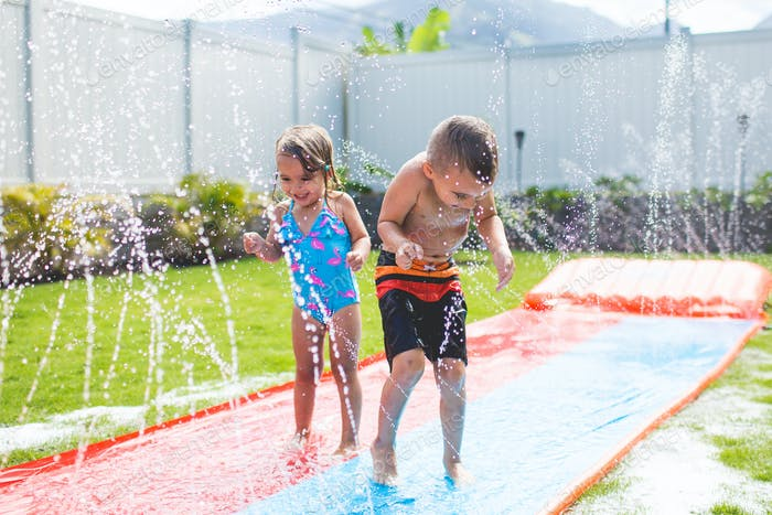 Kids playing in backyard sprinkler