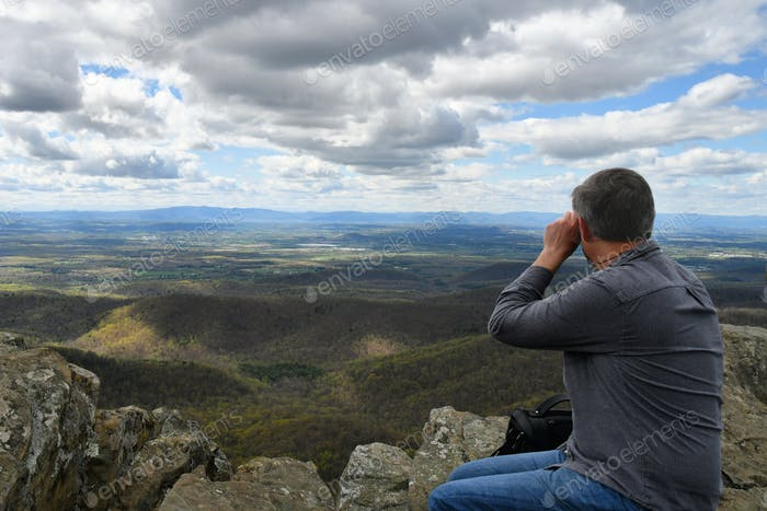 active Baby Boomer Generation X male using binoculars after hiking to the top of a mountain.