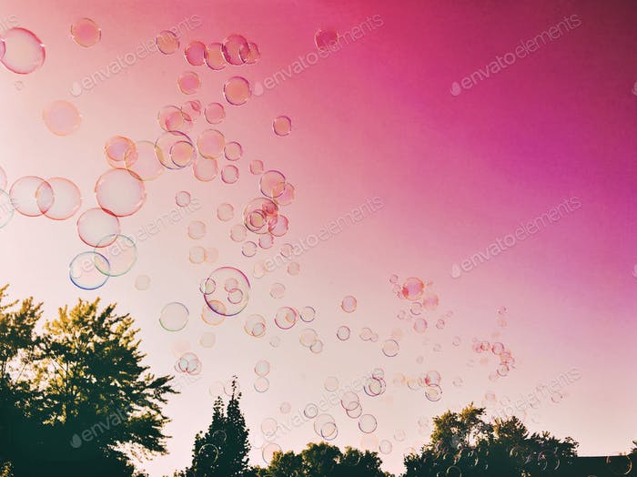 Hundreds of bubbles floating over trees across a bright pink sky.