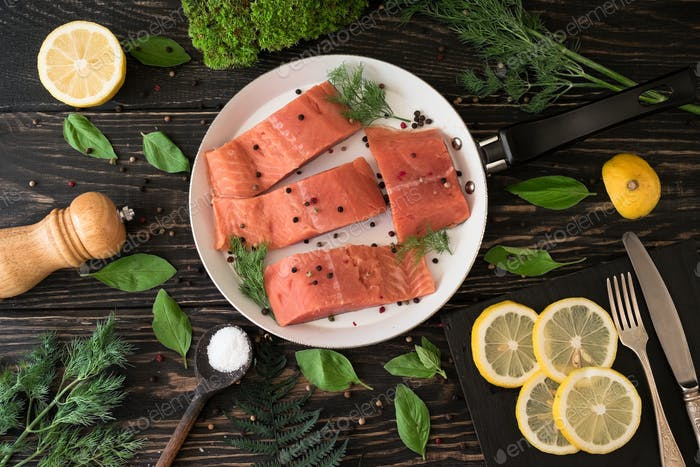 Salmon fillet on rustic kitchen table with fresh ingredients for tasty cooking and frying pan.
