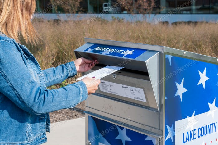 A woman is safely and securely mailing her ballot at an official election drop box
