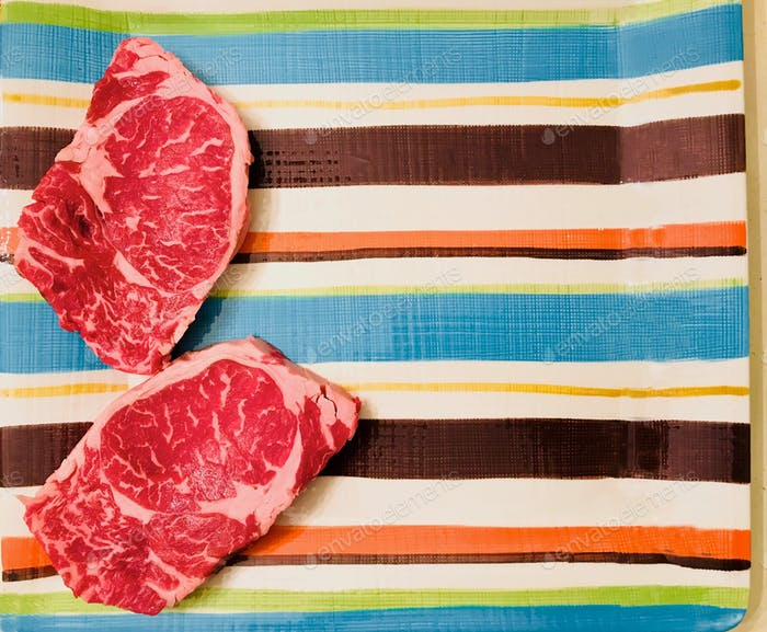 Flatlay Steaks on a Summer platter, ready to barbecue on the backyard grill
