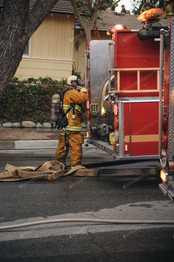 Fire truck and firefighters work to put out a house fire