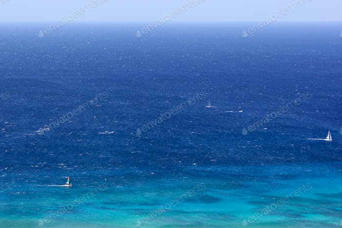 Bright blue ocean full frame with pops of Sailboats - room for copy