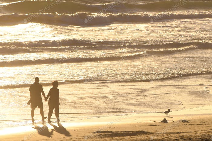 Older couple holding hands and walking along the golden Beach at golden hour right before sunset