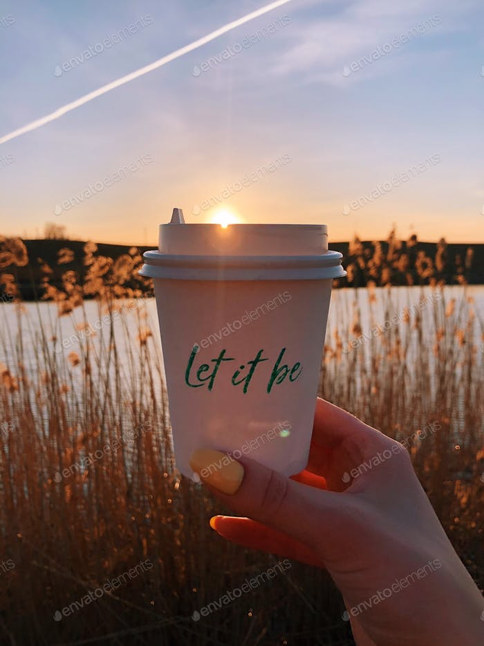 Woman's hand holding a mug in front of sunset. Golden hour